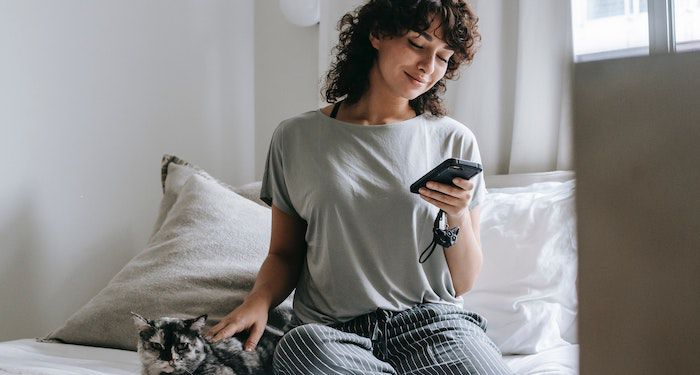 woman smiling at phone and petting cat