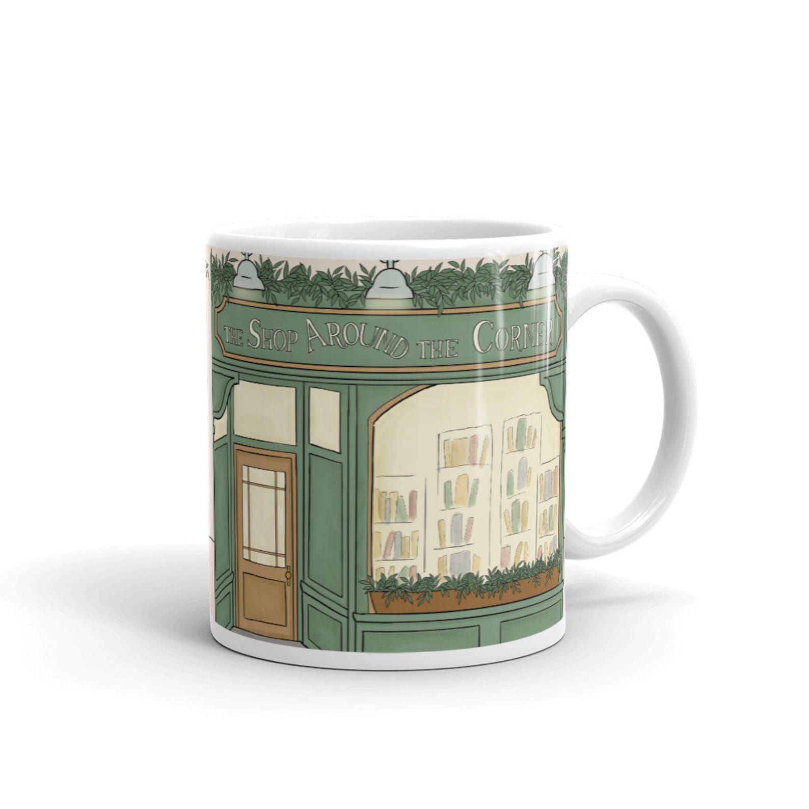 A mug with an image of the storefront of The Shop Around the Corner from the movie You've Got Mail.