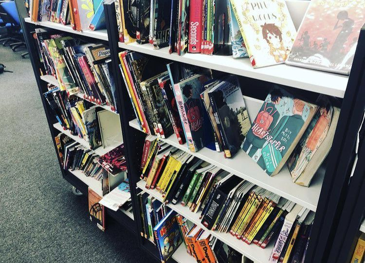 A shelf of comic books with lots of extra room. Some books are faced out.