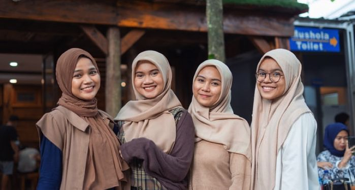 image of four teen girls wearing hijabs smiling at the camera