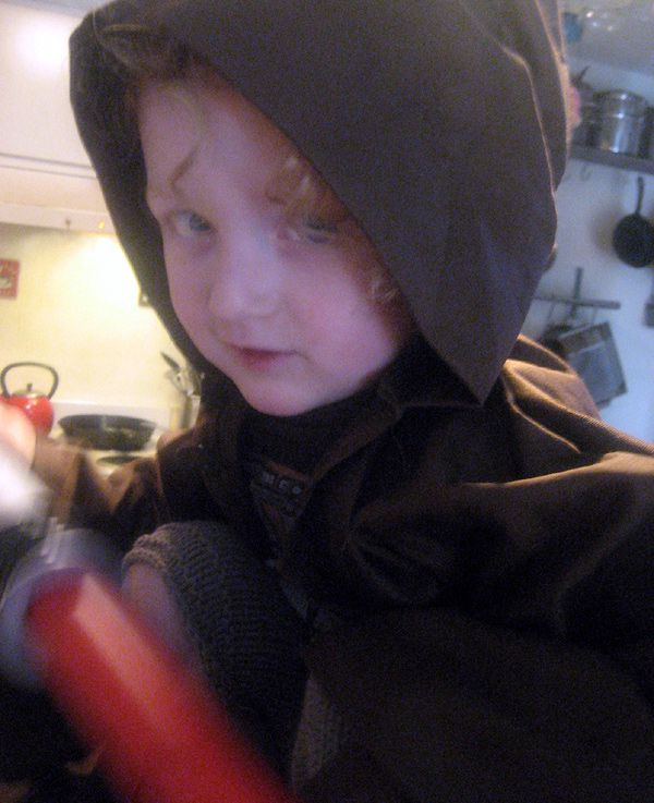 a photo of a child wearing a brown hooded robe and carrying a red plastic lightsaber