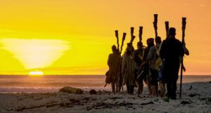 still from Survivor with cast members looks out at sunset