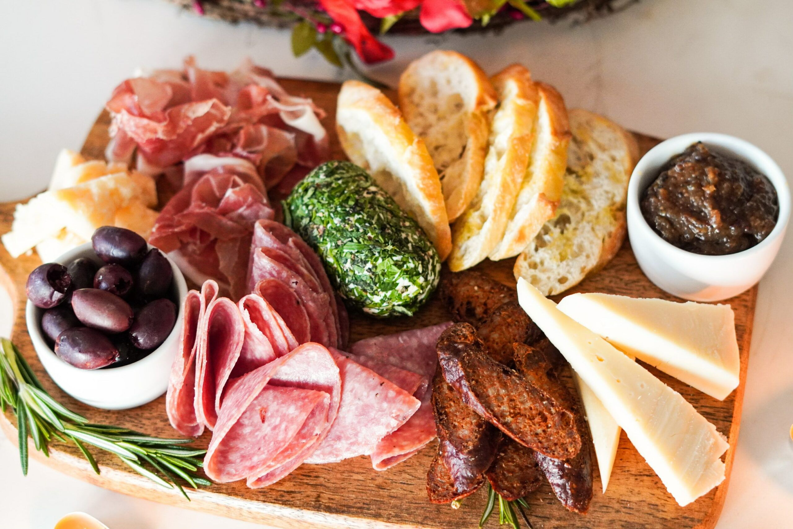 cutting board with olives, deli meat, cheese wedges, and sliced bread
