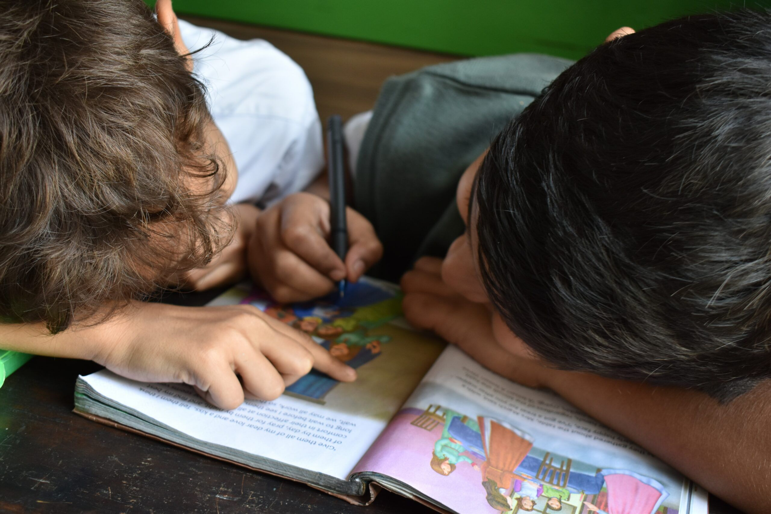 two boys writing on  book