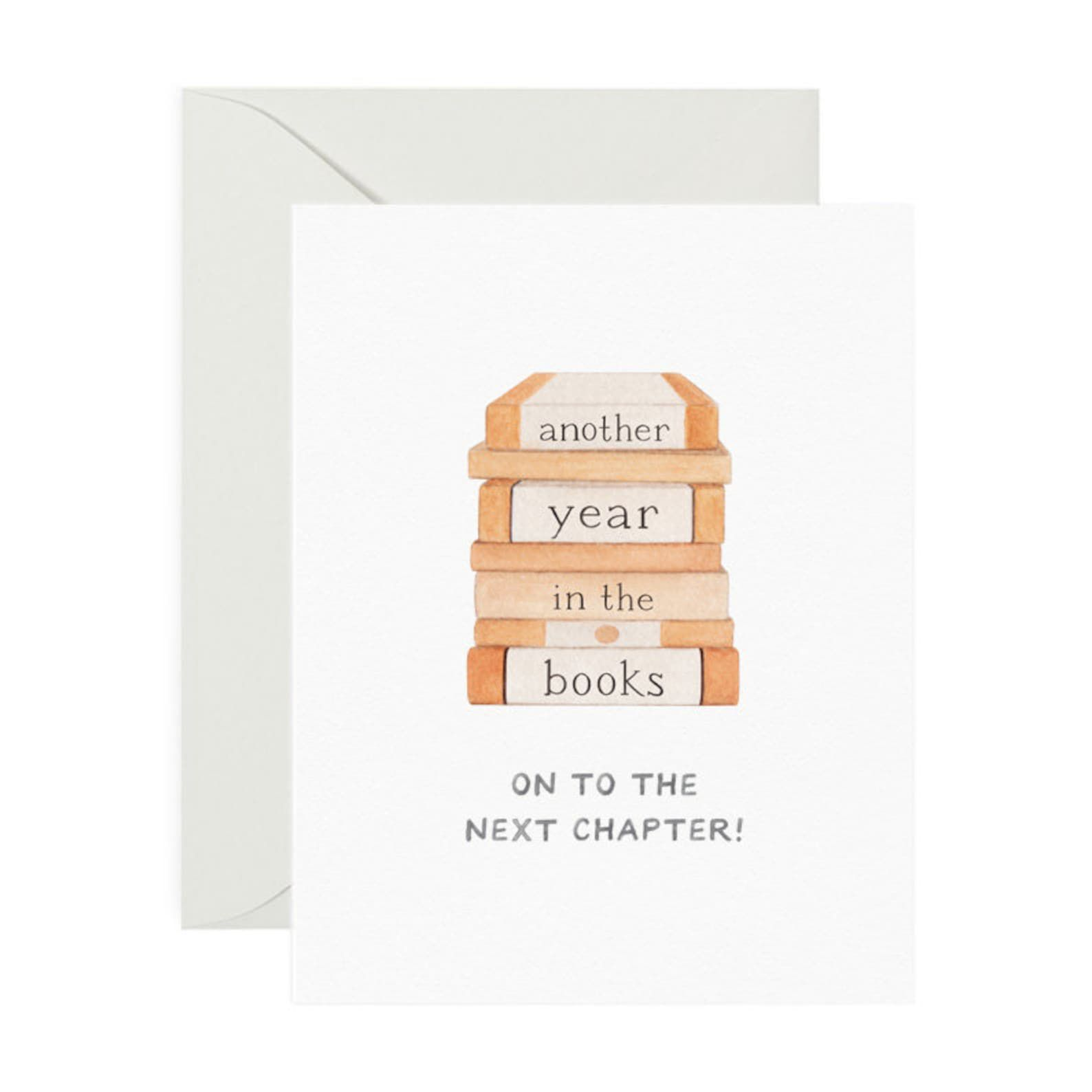 """A stack of books on a white card that reads """"Another Year in the Books - On to the next chapter!"""""""