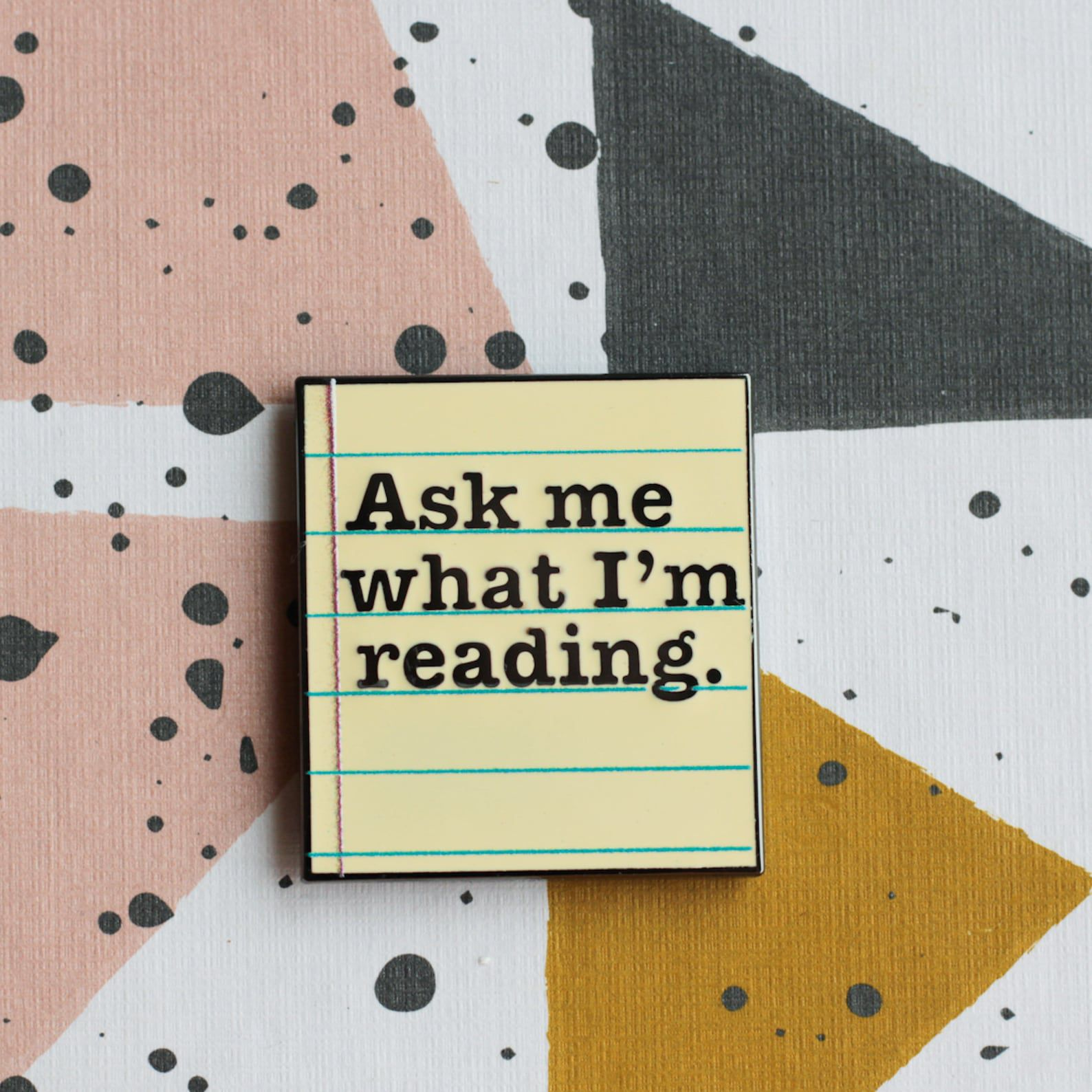 """An enamel pin that looks like a piece of lined paper and reads """"Ask me what I'm reading."""""""