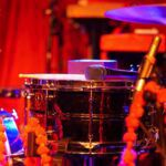 a snare drum, microphone, and high hat drum lit by red light