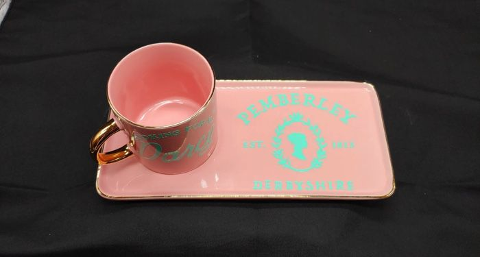 A pink tray with matching mug that reads Pemberley Est. 1813 in blue script.