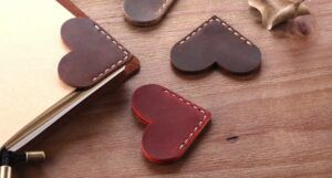 A collection of leather hearts stitched together at the point and used as corner bookmarks.