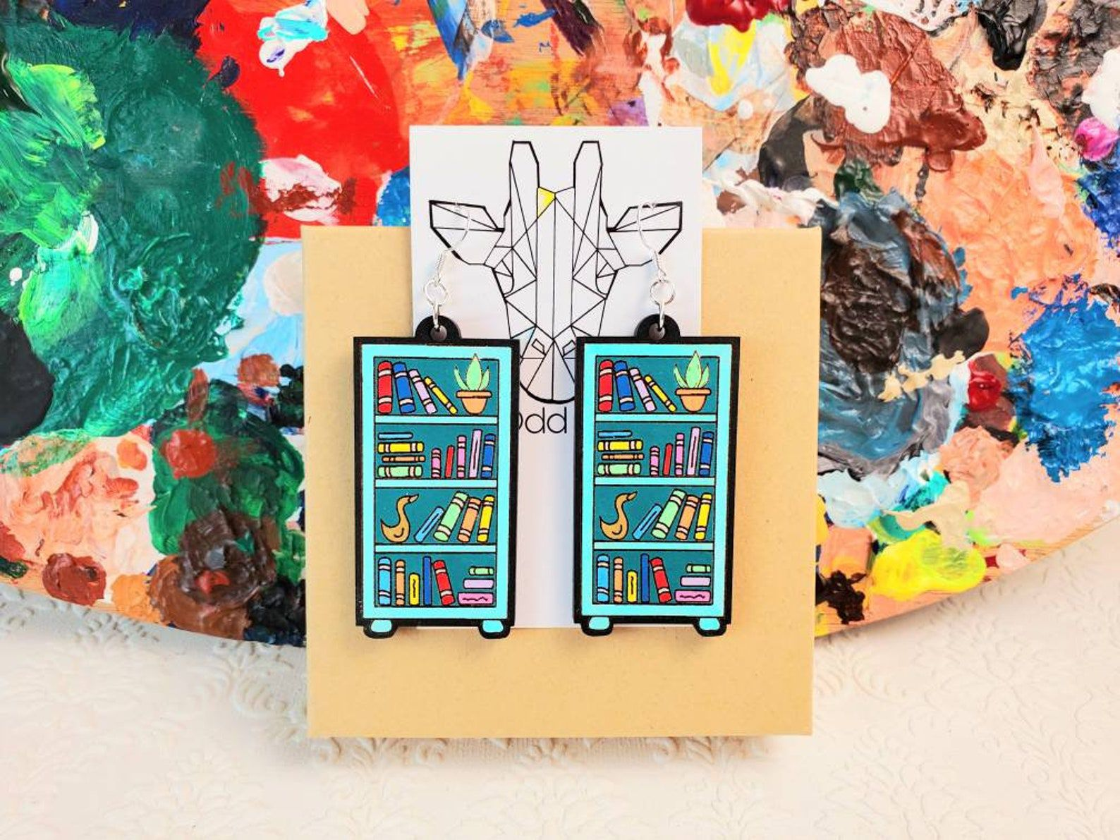 Dangly teal earrings in the shape of bookshelves filled with colorful books and plants.