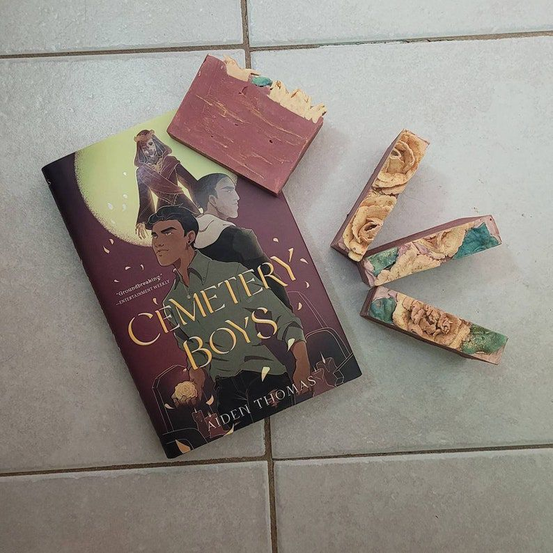 image of the book cemetery boys and next to it bars of soap with the same colours, dark red, gold and green