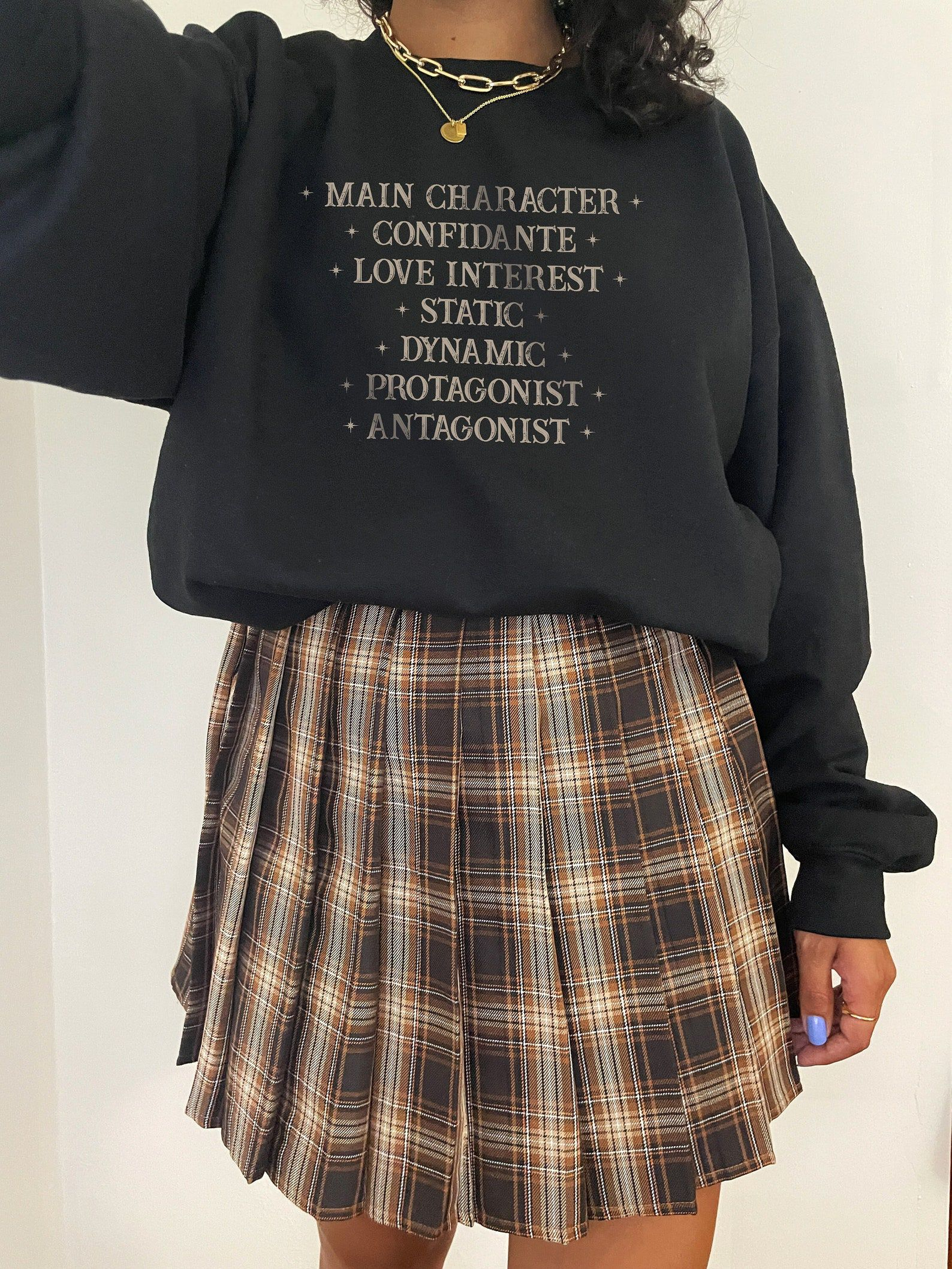 """A black sweatshirt with gold script listing """"main Character, Confidante, love interest, states, dynamic, protagonist, antagonist"""""""