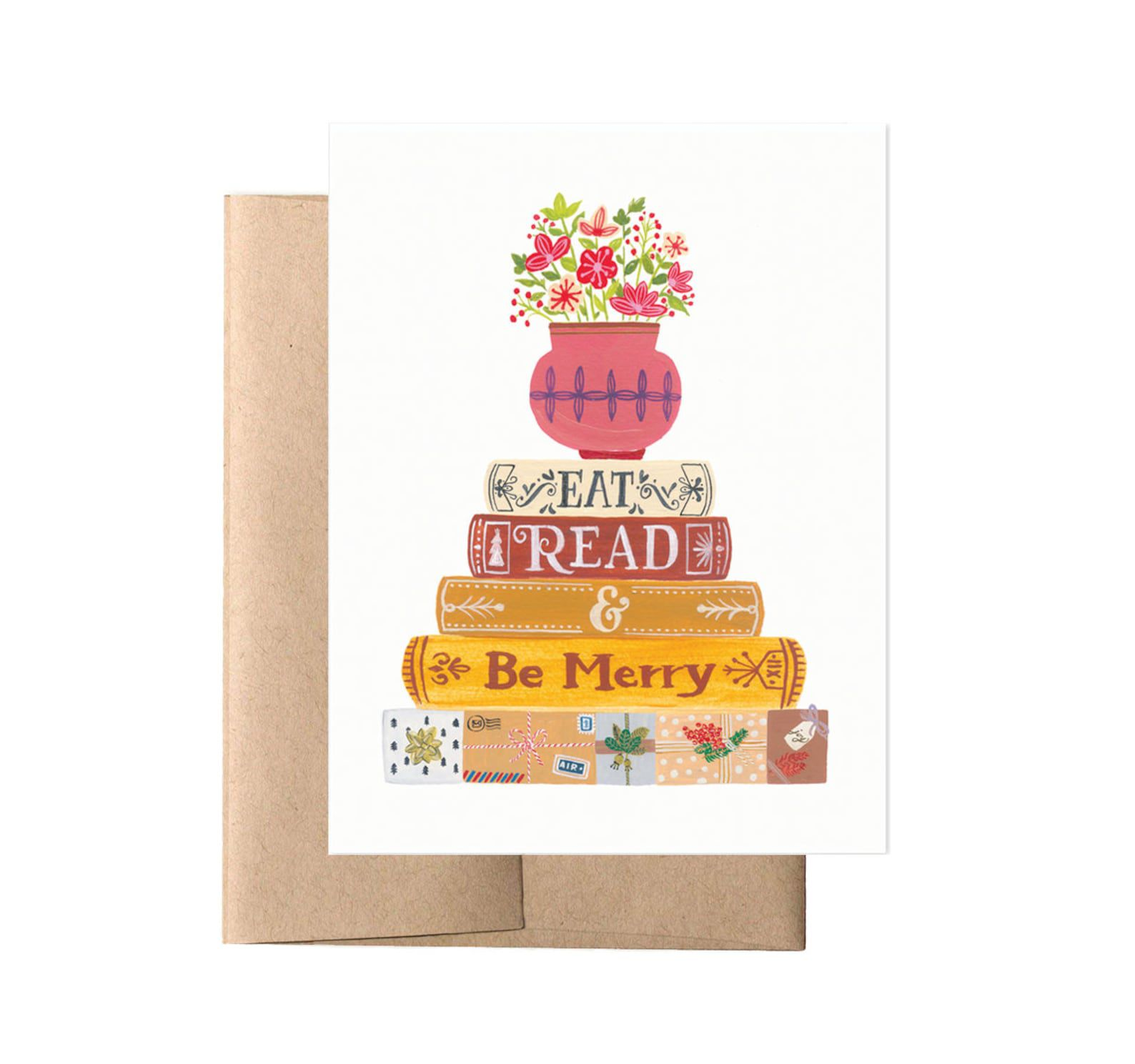 """A stack of bright books with a floral arrangement on top and the words """"Eat, Read, and Be Merry"""" on the spine."""