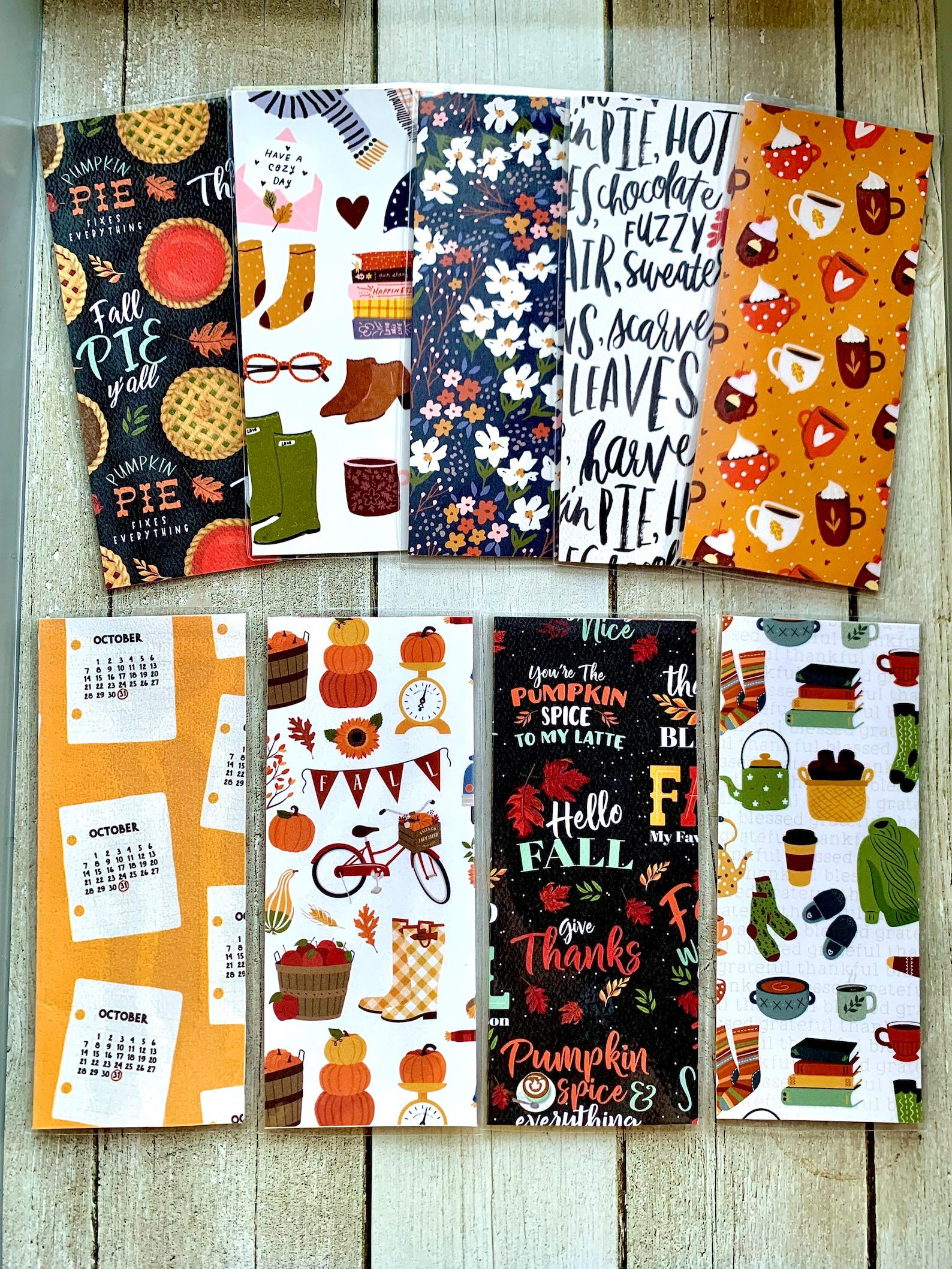Eight bookmarks in various fall motifs of pumpkin spice lattes, green sweaters, fall florals, and pumpkin pies.