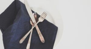 a silver fork, spoon, and knife resting on a blue napkin and white plate