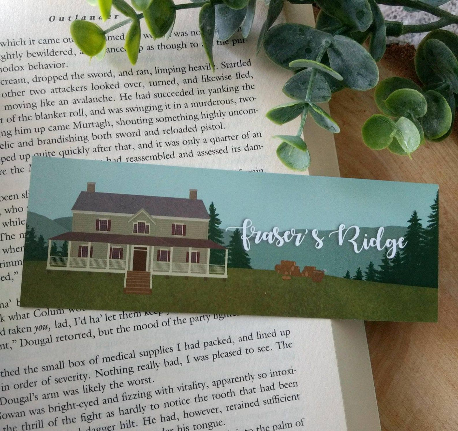 """bookmark depicting blue mountains and a grand house, with the words """"Fraser's Ridge"""""""