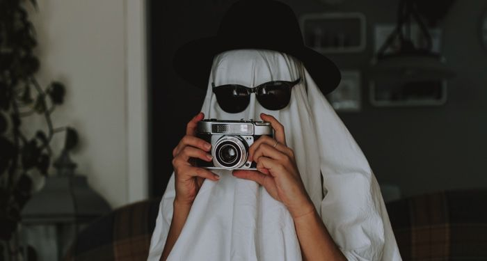 person dressed like a ghost with a sheet over their head plus sunglasses and a hat. The person is holding an old fashioned camera