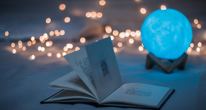 Image of an open book with twinkle lights behind it