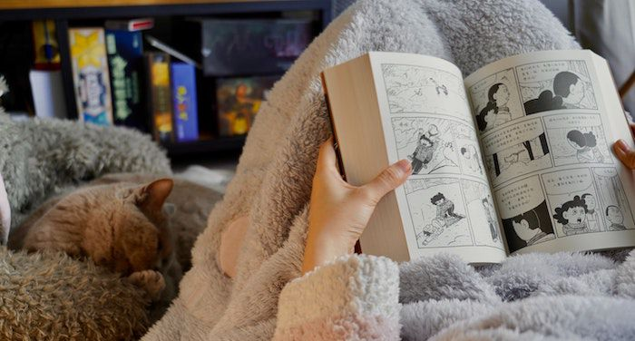 Image of a person holding open a comic