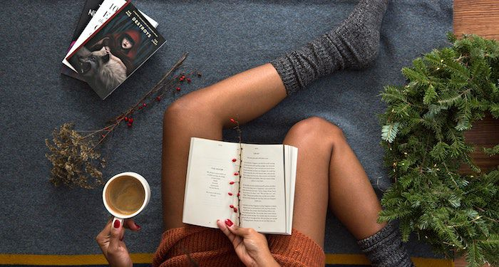 Image of black skin legs with socks, a book, and cup of coffee