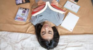 Image of a person with olive skin and dark hair reading a book