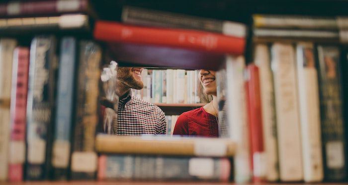 Image of a couple smiling behind a frame of books