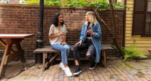 Image of two teen girls sitting on a bench. One is brown skinned and one is olive skinned.