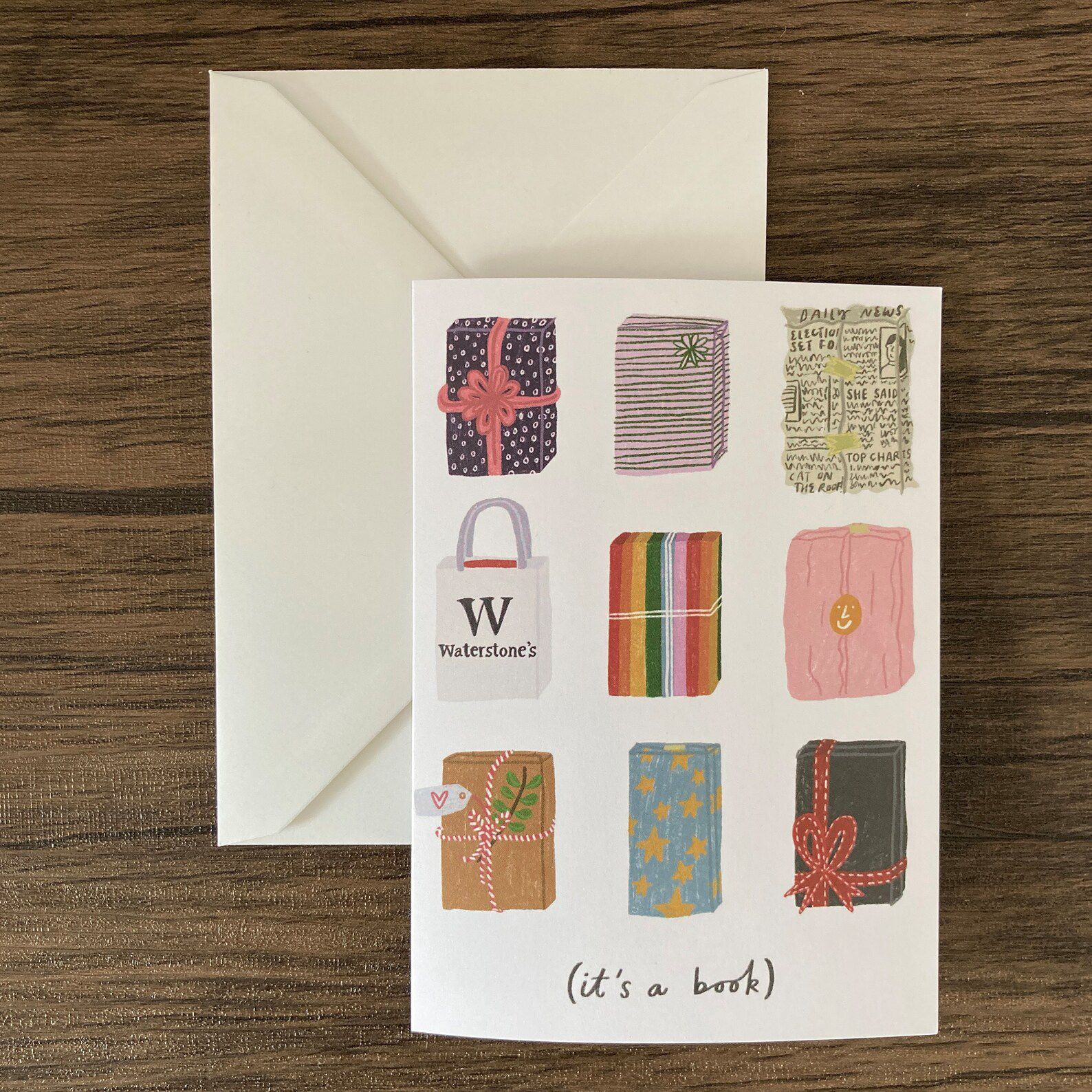 """A card with a bunch of wrapped packages in various types of wrapping paper, and words that read """"it's a book"""""""