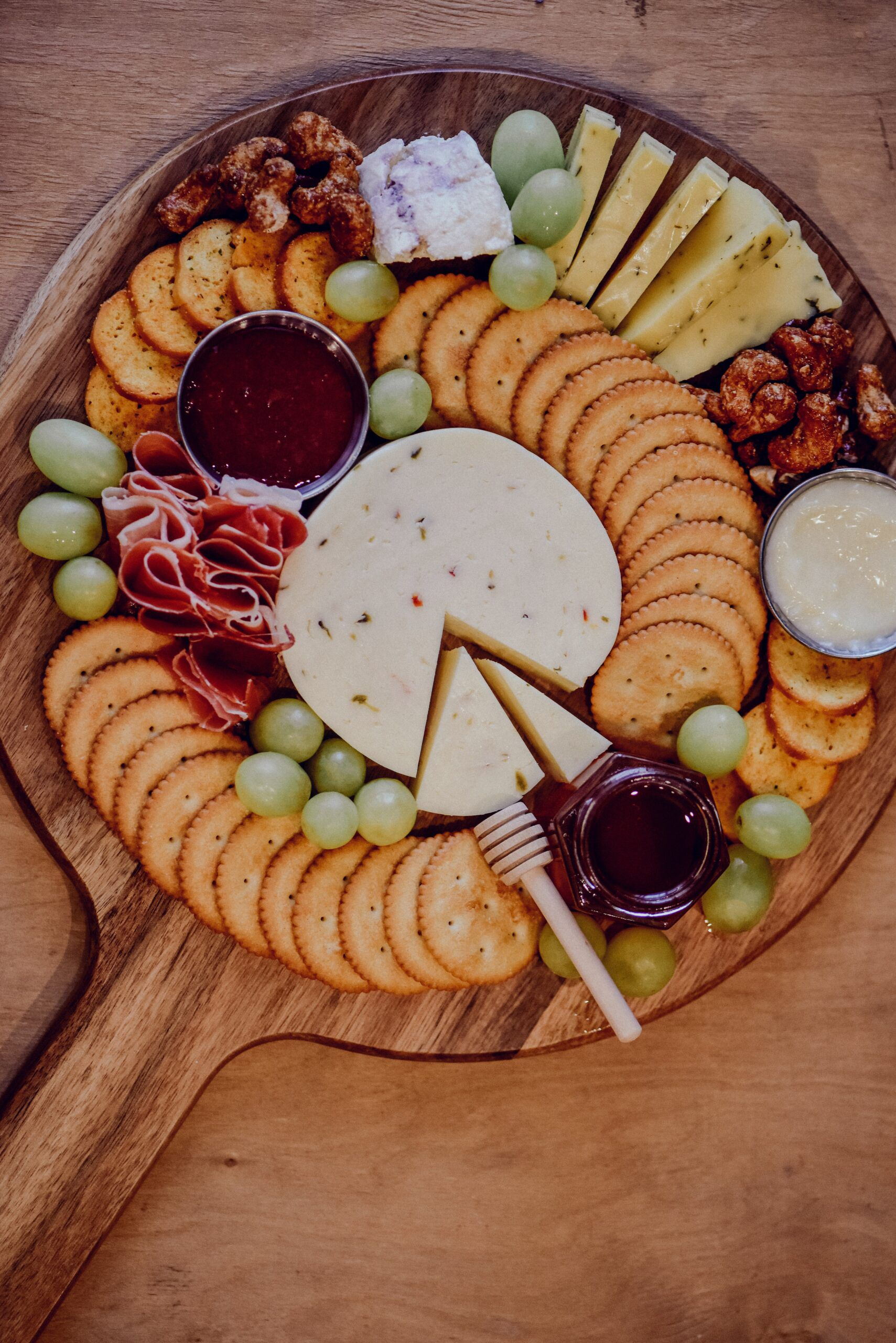 cutting board with handle holding crackers, jam, cheese, meat, and fruit