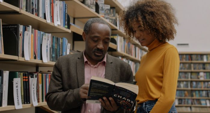 two people reading a book in library stacks