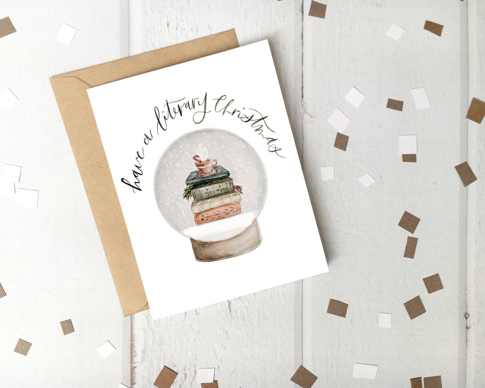 """A white card reads """"Have a literary Christmas"""" and depicts a snowglobe with a stack of books and a cup of hot cocoa inside."""