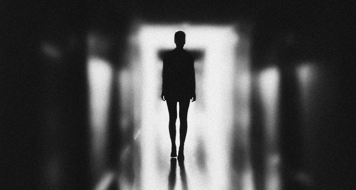 eerie black and white image of a person in silhouette