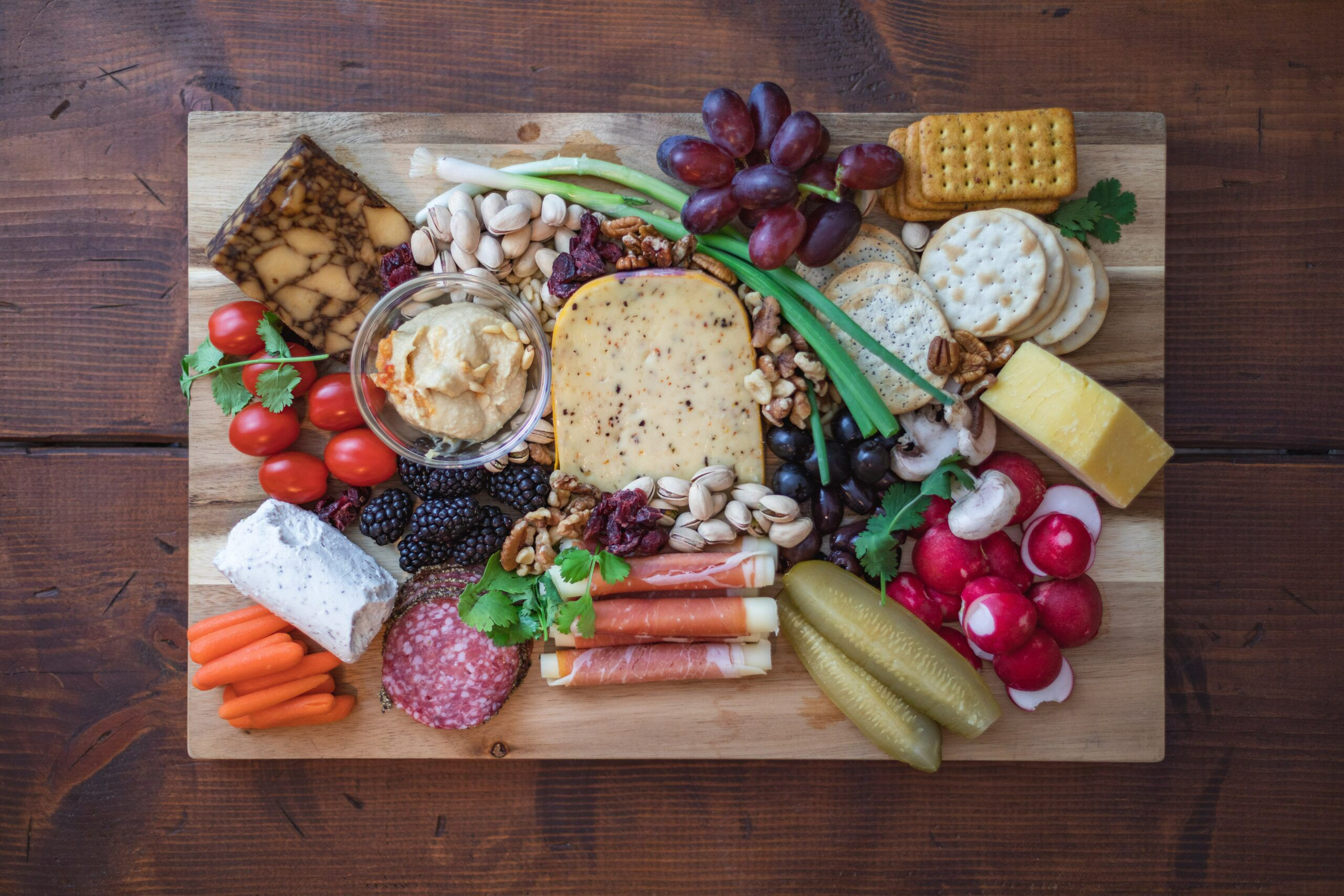 cheese, meat, fruit, and vegetables on cutting board