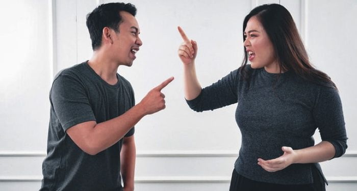 man and woman pointing fingers at each other arguing