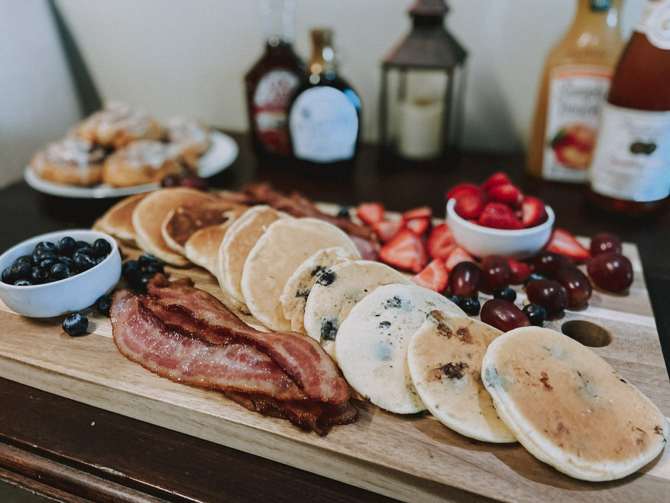 pancakes and bacon on cutting board with fruit