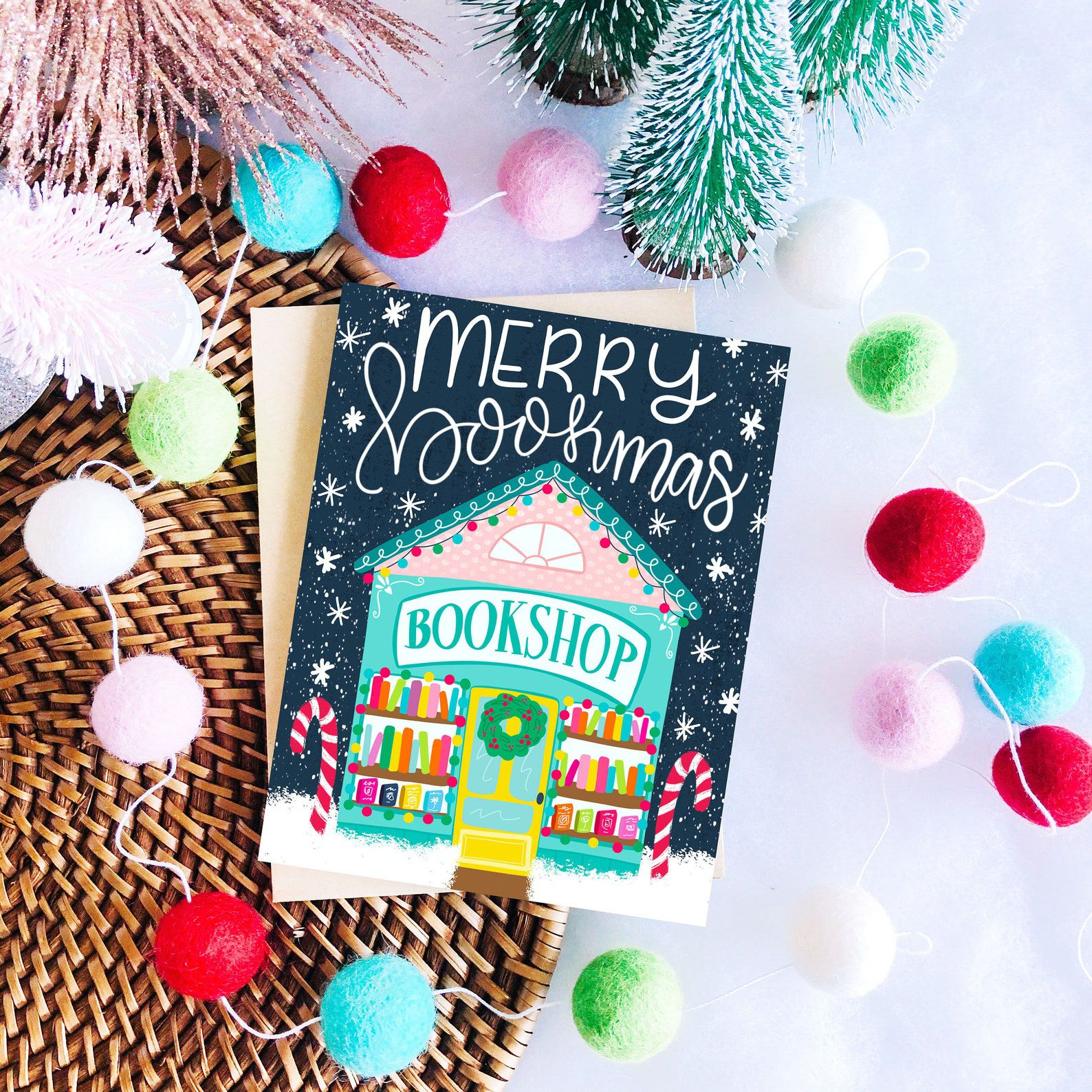 """A dark blue card that reads """"Merry Bookmas"""" and depicts a teal bookshop with colorful books pines and pink, red, and green accents."""