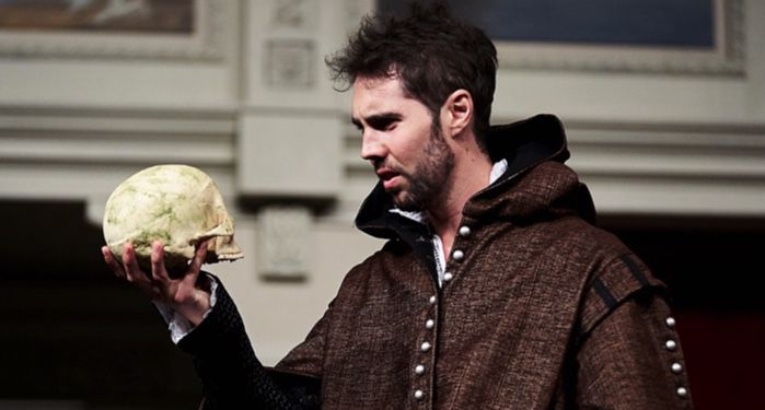 a stage actor playing Hamlet, holding.a skull