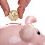 a hand placing a gold coin into a pink piggy bank