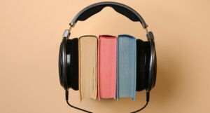 black corded headphones wrapped around a stack of colorful books
