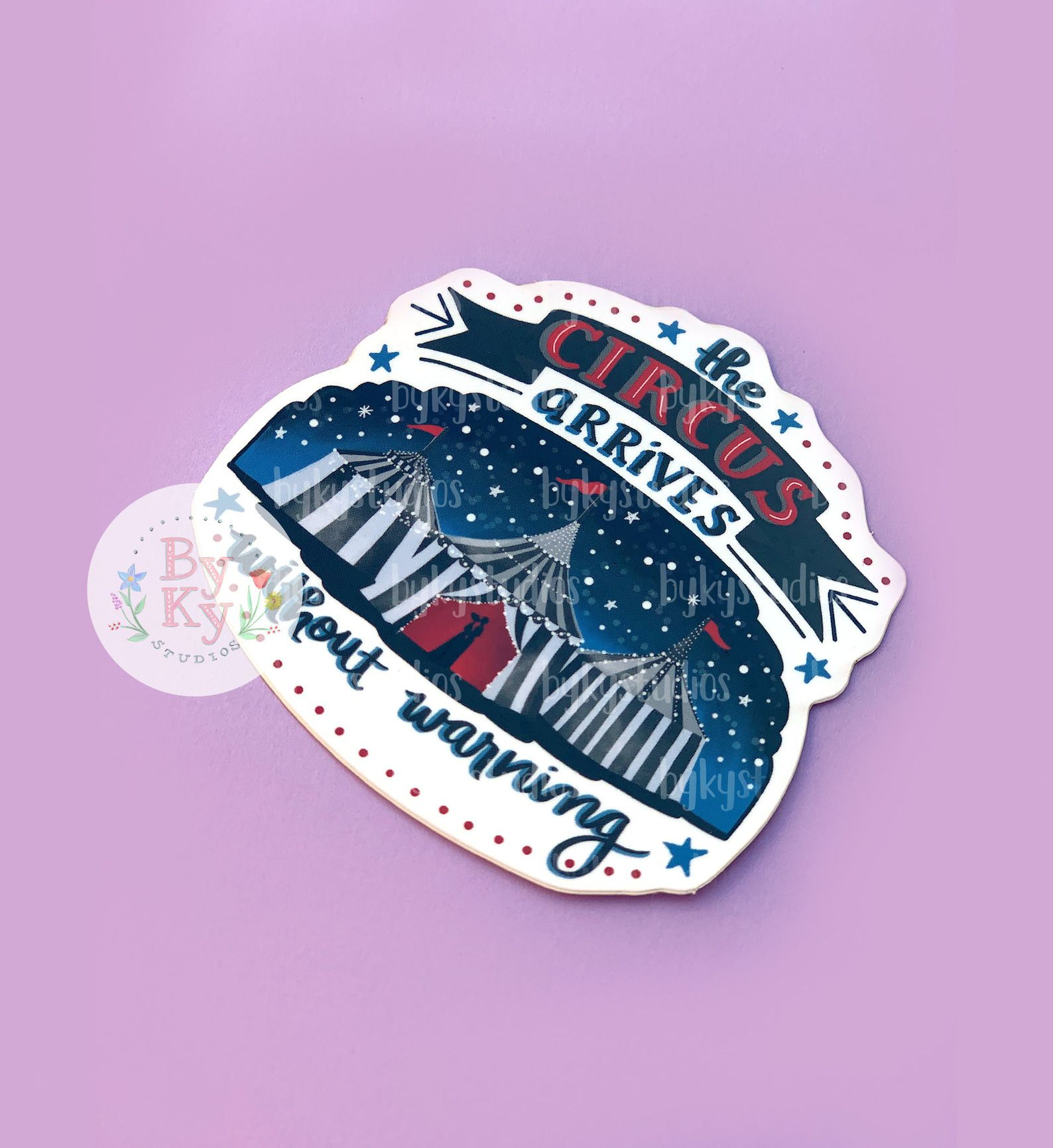 """A sticker depicting an image of a circus tent with the words """"The circus arrives without warning."""""""
