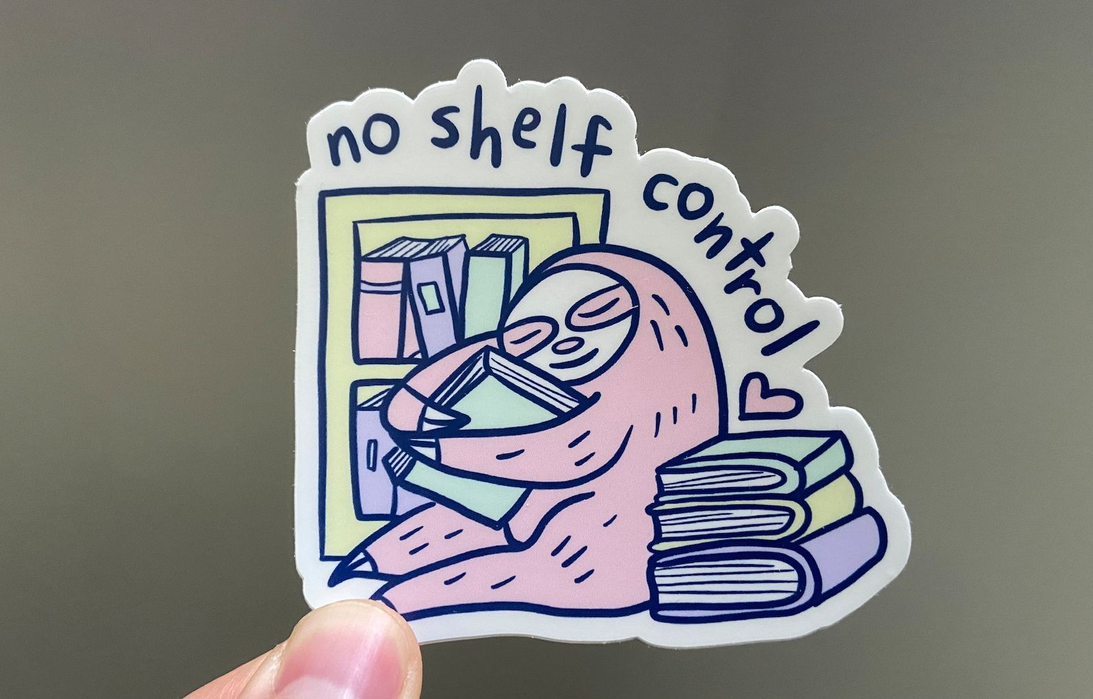 """A pink sloth hugs a stack of books on a sticker that reads """"so shelf control"""""""