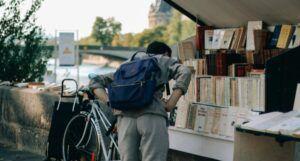 a person browsing a riverfront bookshop in Paris, France