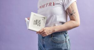 person with poetry shirt holding book