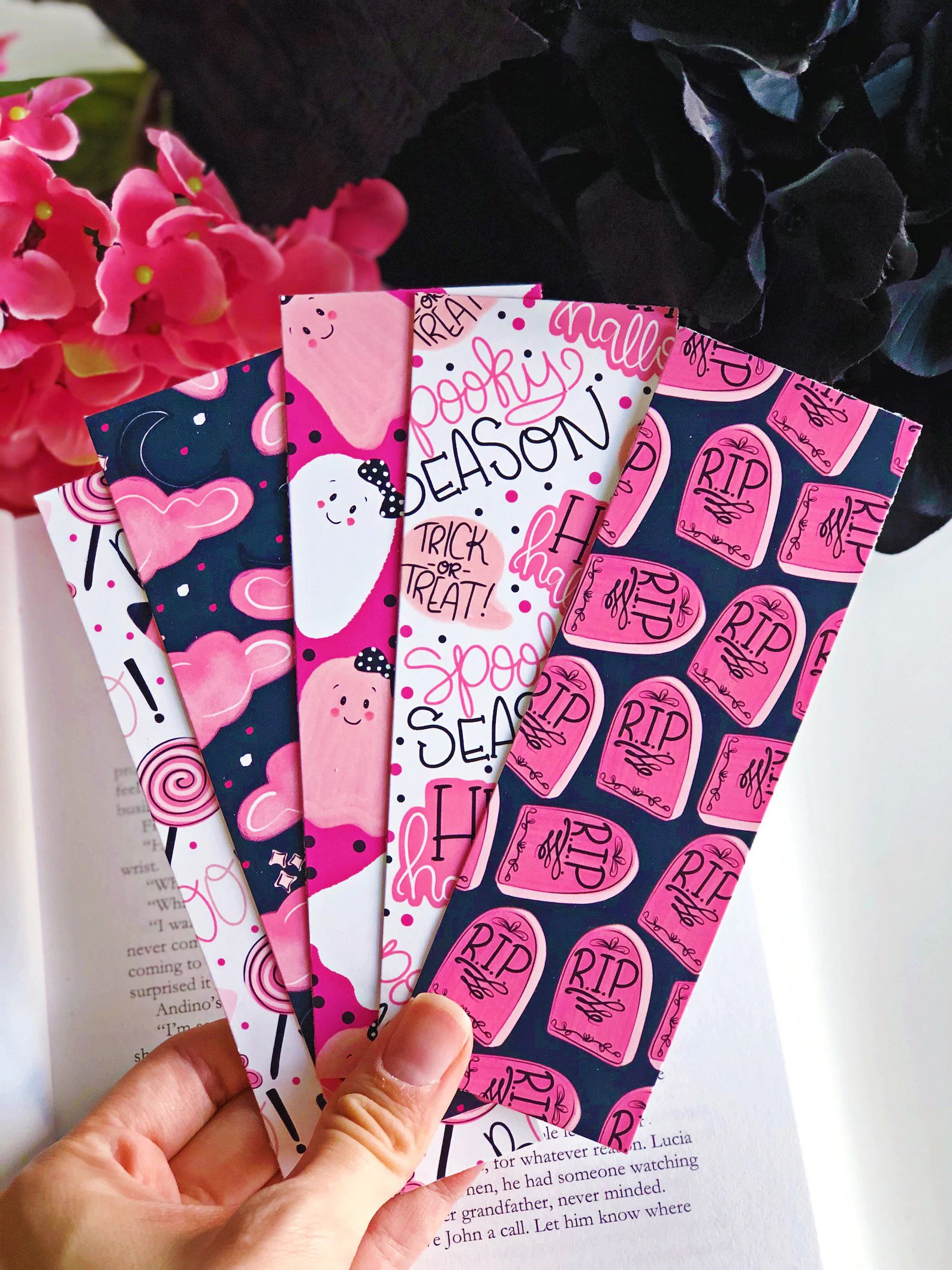 a collection of five pink, white, and navy blue bookmarks with spooky season and ghost motifs