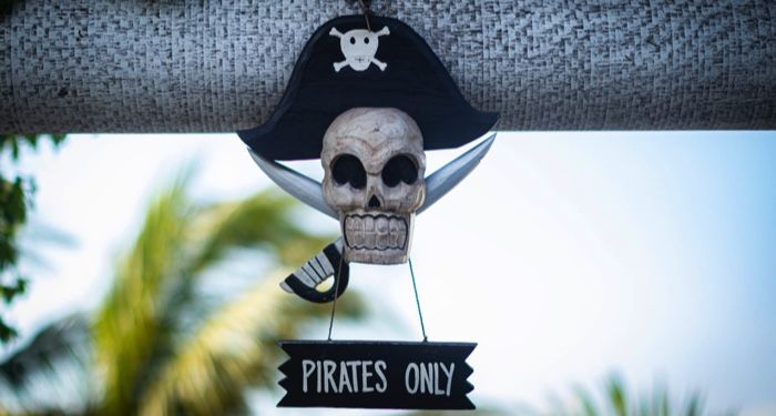 """a decorative skull & crossbones with a sign hanging form it that reads:""""pirates only"""""""