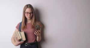 a woman holding a stack of books in one hand holding up a mobile phone in the other