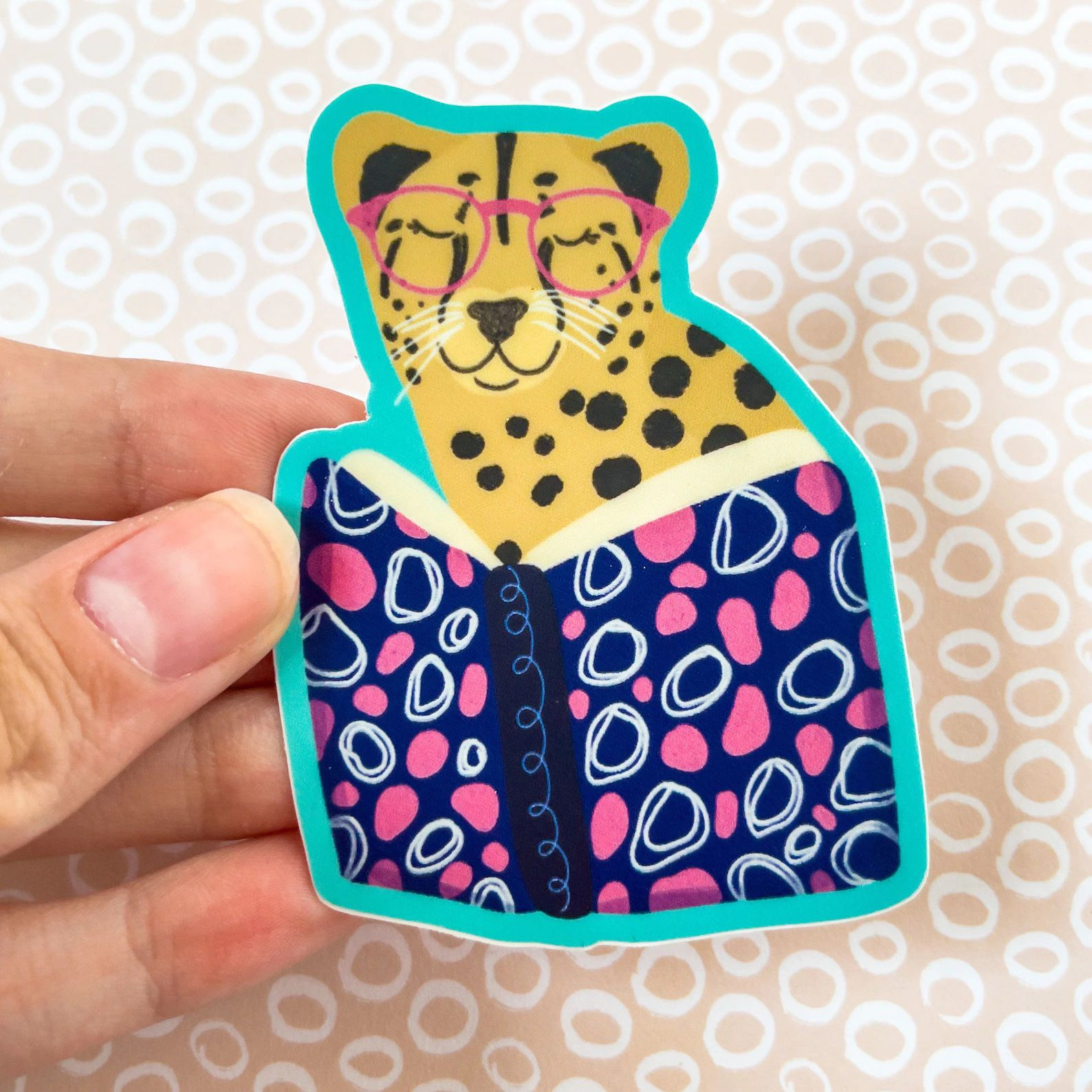 A sticker depicting a cheetah in pink glasses reading a book that is decorated with blue, pink, and white squiggles.
