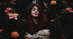 red headed girl around flowers