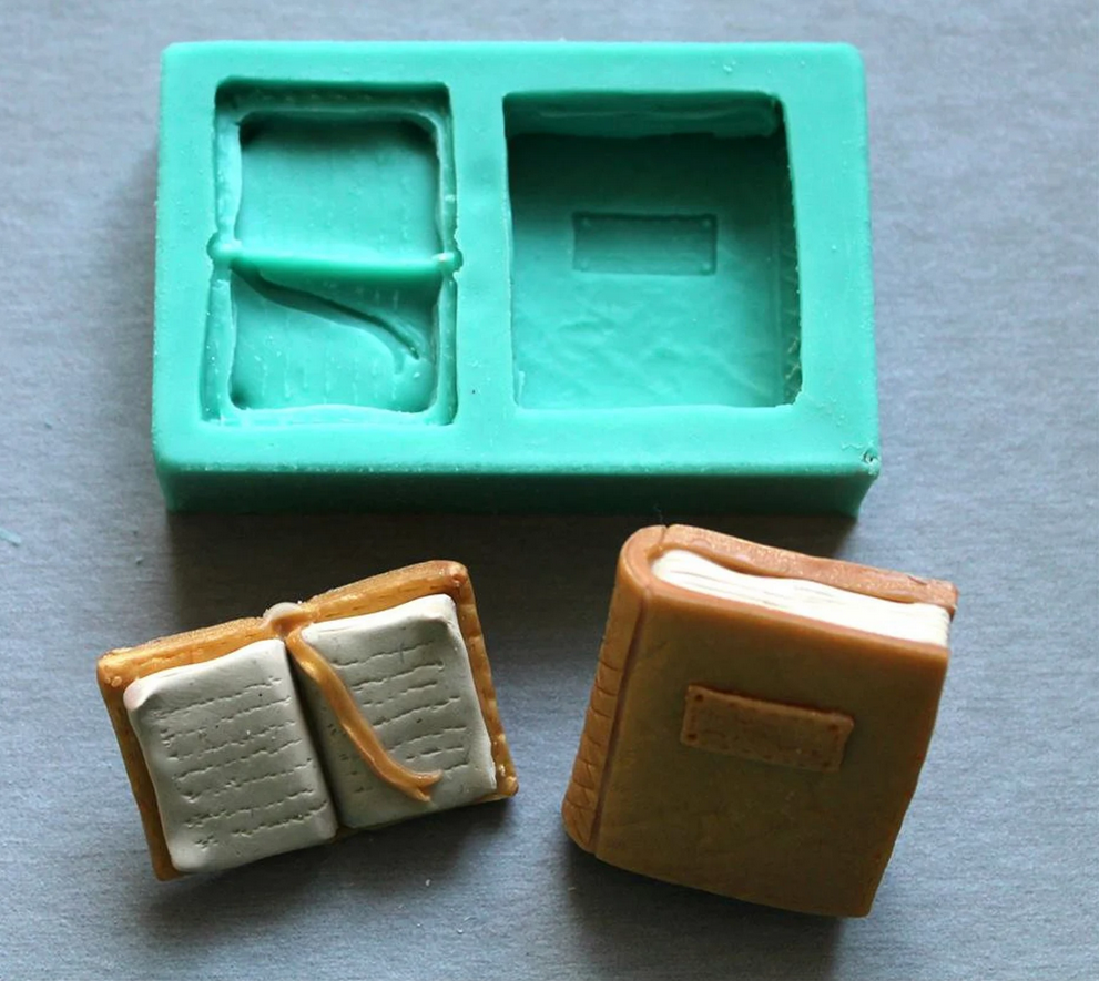 image of a mold showing one closed book and an open book