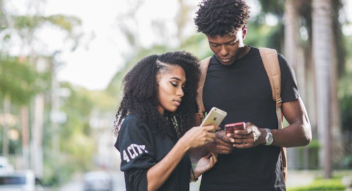 Image of two Black teens looking at their phones